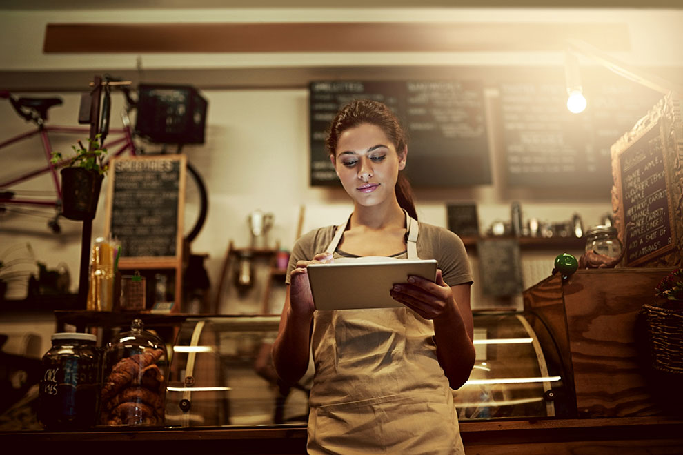 Woman using tablet in bakery with modern lighting